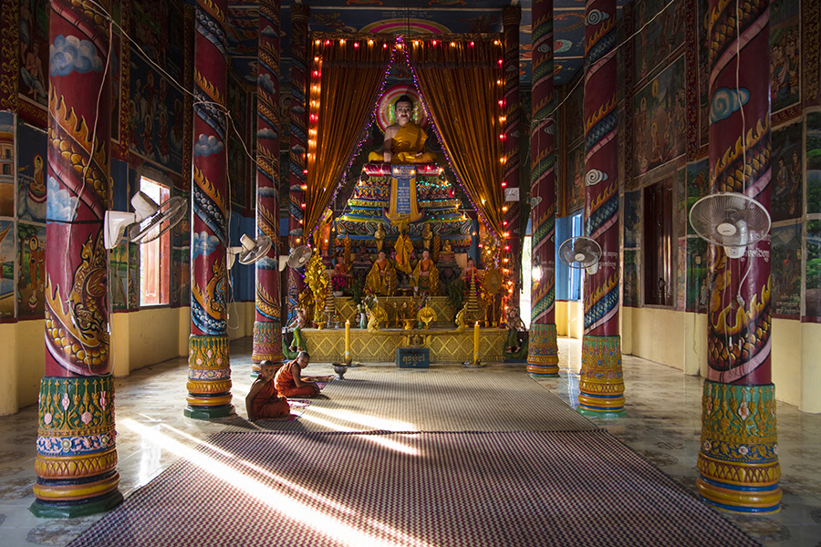 Young Buddhist monks sit in front of shrine inside temple, Preah Prosop, Mekong river, Kandal, Cambodia