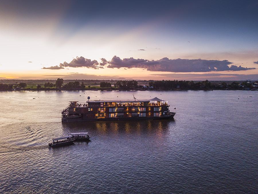 Aerial of Skiff auxiliary launch boats approaching river cruise ship Aqua Mekong (Aqua Expeditions) on Tonle Sap river at dusk, Kampong Prasat, Kampong Chhnang, Cambodia