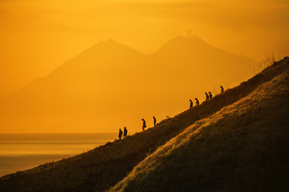 Tourists hiking down a hill at sunset, Komodo Island, Indonesia
