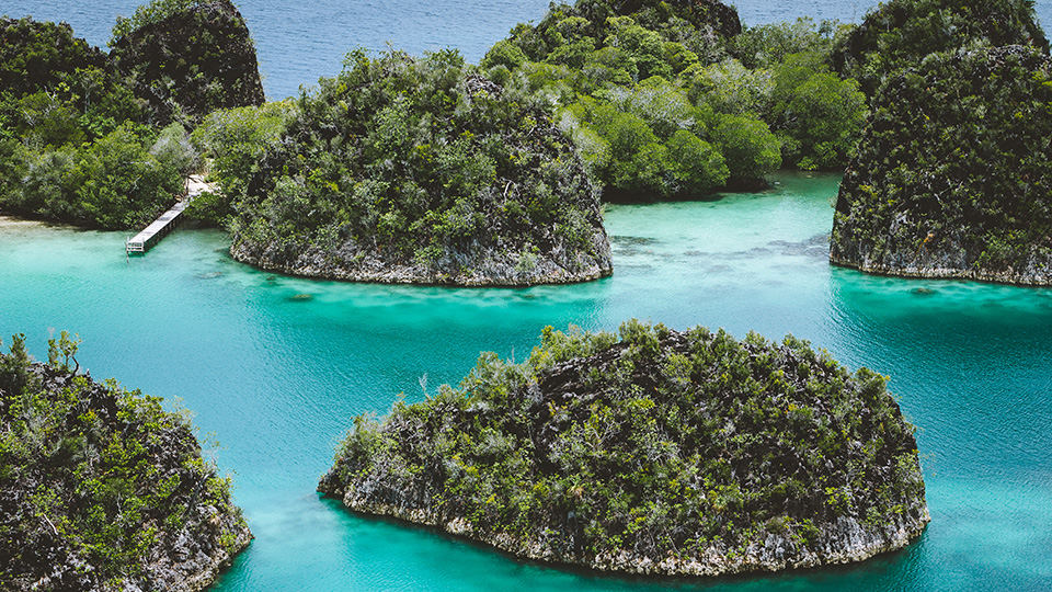 Pianemo Islands. Group of small island in shallow blue lagoon water, Raja Ampat, West Papua, Indonesia